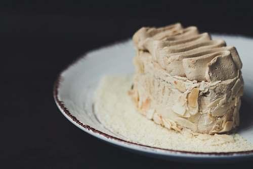 dessert beige icing-covered cake on plate cream