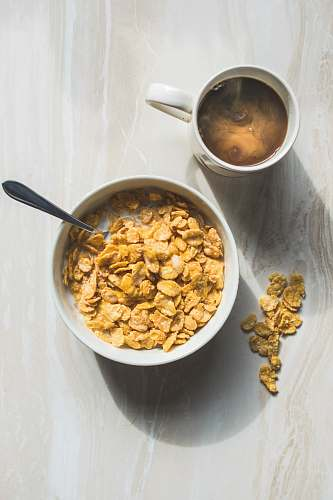 breakfast ceramic bowl filled with cereals and spoon bowl