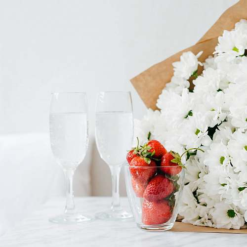 strawberry red strawberries filled glass cup beside white flower bouquet bedside