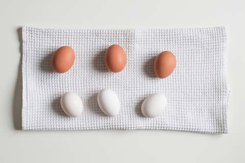 medication six white and brown eggs on white towel pill