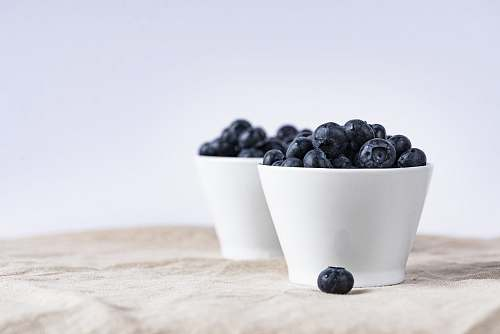 fruit two white ceramic cup filled with blueberries fruit place on brown textile blueberry