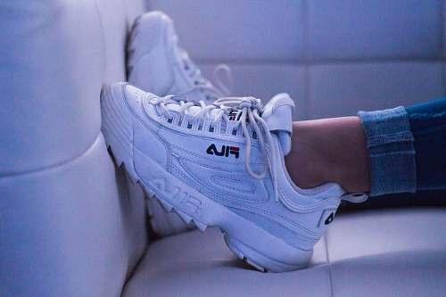 clothing woman wearing white Fila shoes shoe