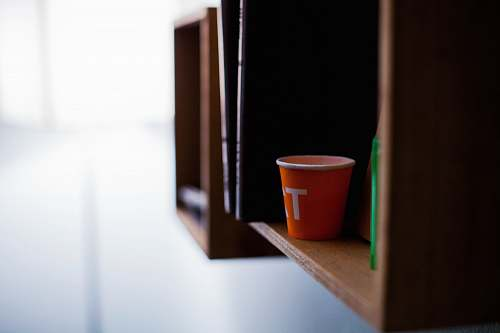 shelving red disposable cup on brown wooden shelf shelf