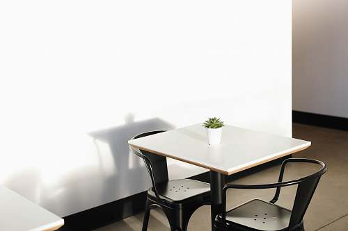 table square white wooden table with two black metal chairs dining table