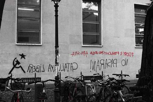 bike black and red text vandals on wall near parked bicycle italy