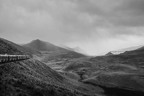 nature grayscale photo of train beside of mountain during cloudy sky black-and-white
