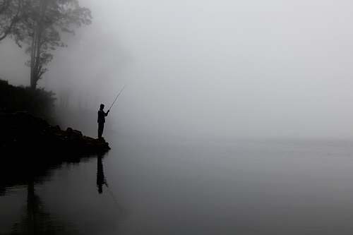 fishing man fishing on calm water behind tree fog