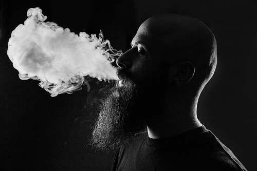 black-and-white man smoking with black background smoke