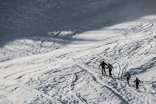 mountain people walking on snow covered ground during daytime san pellegrino pass