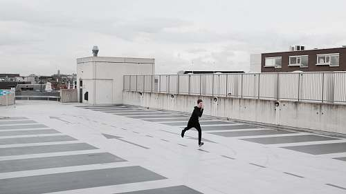 building person running on concrete lot during daytime parking