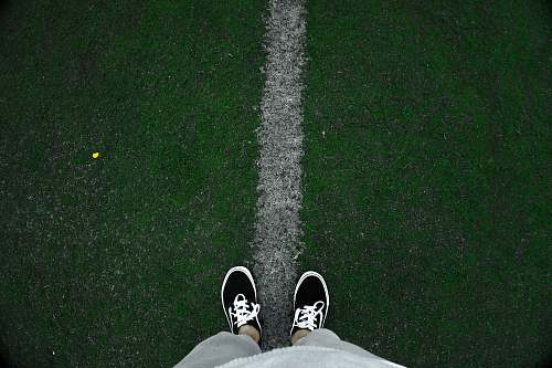 shoe person wearing black low-top sneakers standing on green grass at daytime clothing