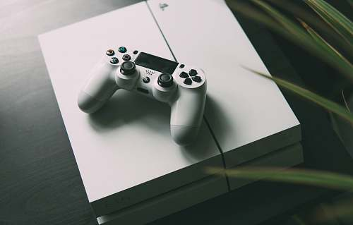 game selective focus photography of white Sony PS4 console with wireless controller table