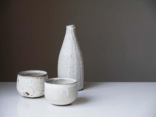 sake two white ceramic bowls and bottle on white table beverage