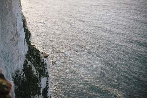 water white rocky mountain next to ocean ripple
