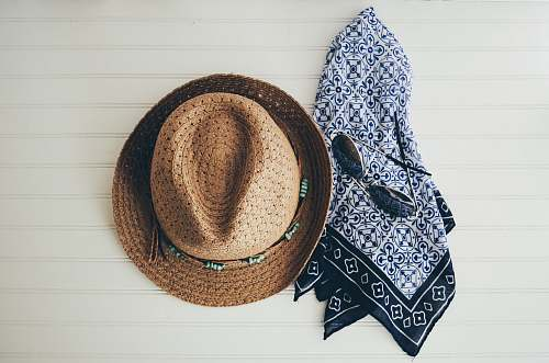 sunglasses brown hat beside black handkerchief scarf