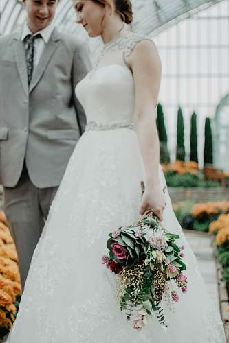 person bride walking with groom on aisle holding flower boquet people