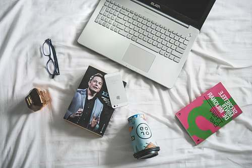 person flat lay photography of MacBook and book with eyeglasses people