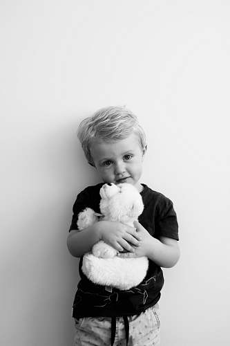 person grayscale photography of boy holding bear plush toy black-and-white