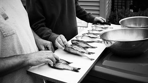 black-and-white grayscale photography of two people in front of fish on table fish