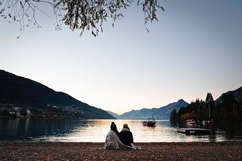 boat man and woman sitting on sea shore person