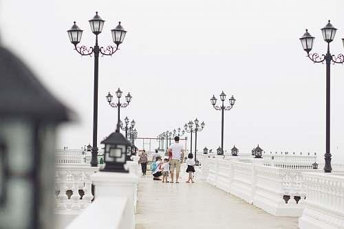 person man holding children walking near white light post white