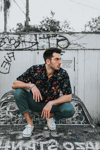 person man in black, blue, and red floral button-up collared shirt and gray pants sitting on car hood during daytime people