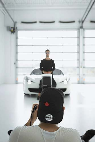 people man taking a picture of standing man in front of car inside room person