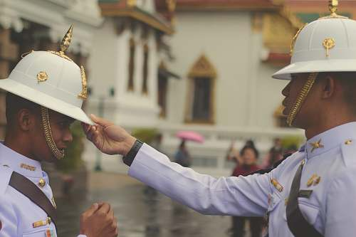 person officer in white uniform touching man's white hat people