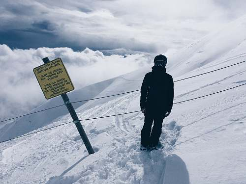 nature person in snowsuit standing beside sign outdoors