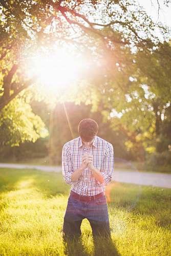 people photo of man kneeling on grass near tree light