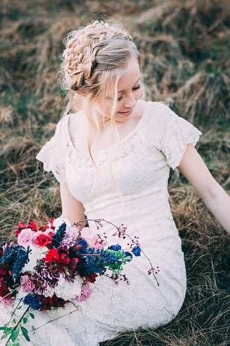 person woman holding bouquet of flowers siting on hay people