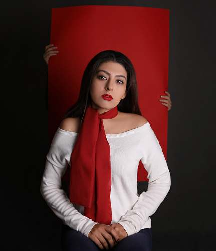 person woman in white long-sleeved top and red scarf in front of red paper board people