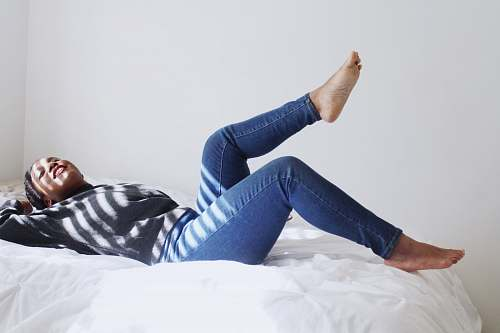 person woman laying on white bed people