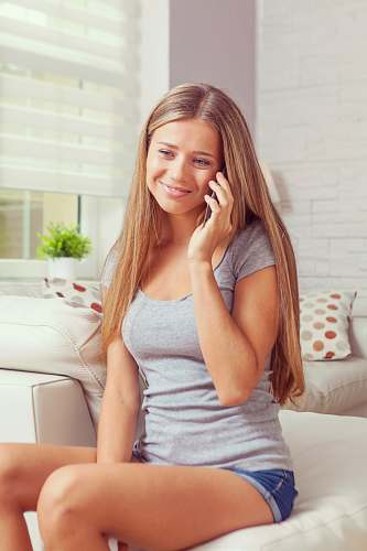 person woman sitting on sofa while holding smartphone people