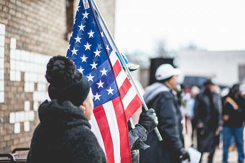 person woman standing beside person holding flag of America people