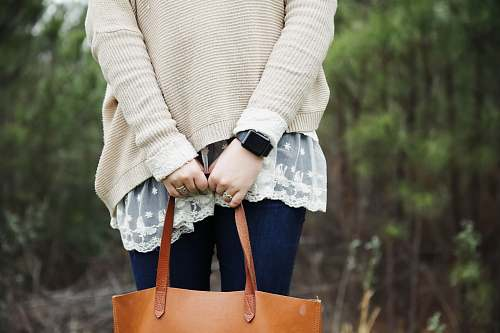 person woman standing holding a brown leather tote bag people