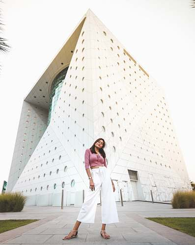 apparel woman standing near white concrete building clothing