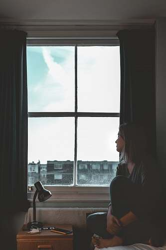 person woman wearing black leggings sitting besides window white
