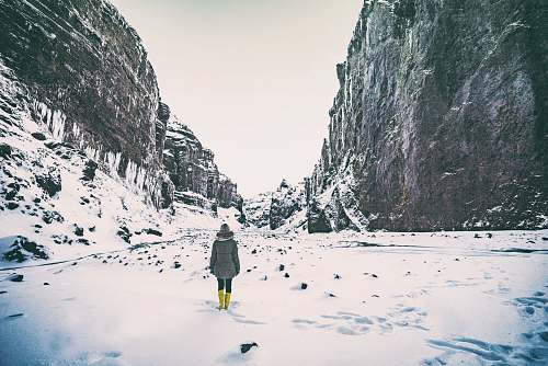 ice woman wearing gray coat standing in between mountain coated by snow nature