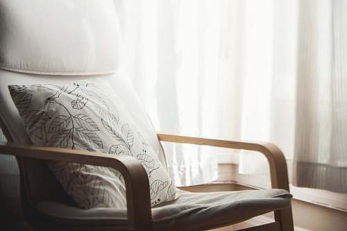 pillow white and grey leaf-printed pillow on armchair furniture