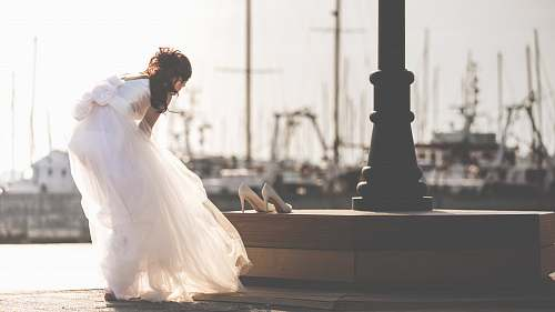bride woman taking off her shoe near post white