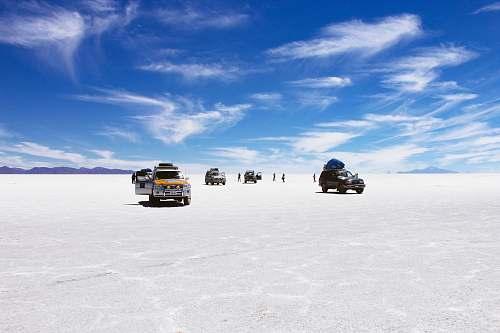 desert sports utility vehicles on desert under cloudy blue sky during daytime uyuni