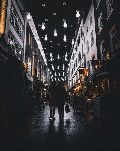 urban silhouette of couple walking under light bulbs between buildings city