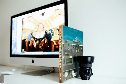 screen selective focus photography of black camera lens beside book and turned on iMac office