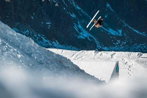 snow biplane flying near mountain outdoors