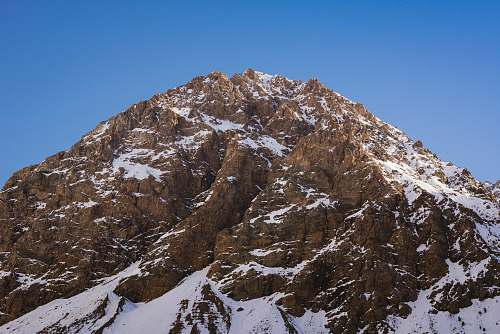 crest close up photo of brown snowcapped mountain at daytime mountain range