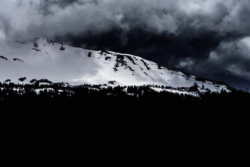 sky grayscale photo of mountain during winter outdoors