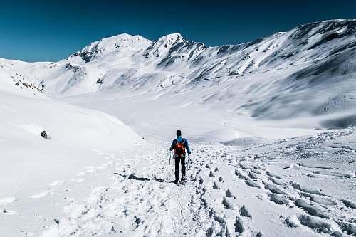 nature man walking on snow field near mountain snow