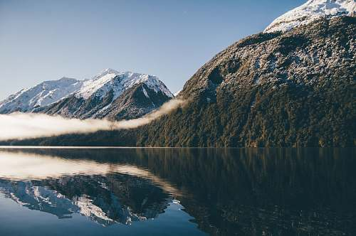 nature mountain reflecting on body of water snow
