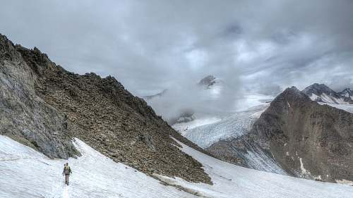 snow person walking on snow covered mountain during daytime glacier